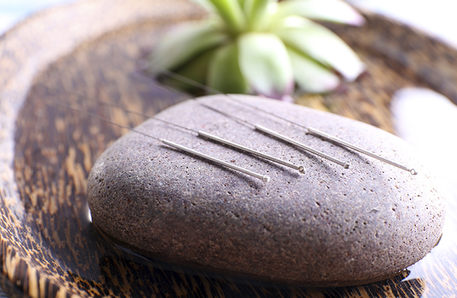 Acupuncture needles on a stone