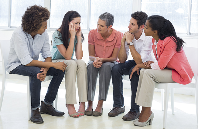 Group sitting in circle for therapy session.